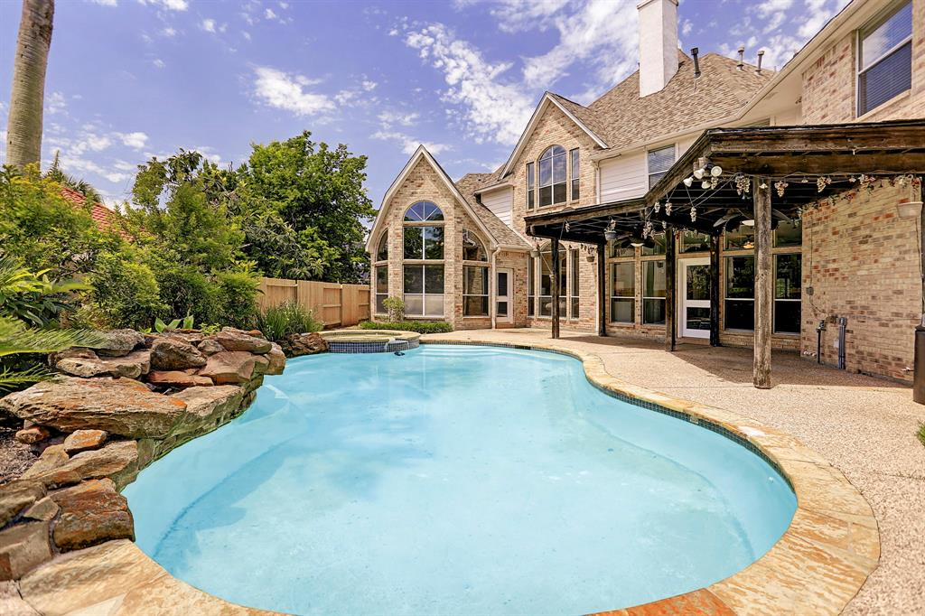 Lovely brick home with a pool located on a corner lot in prestigious Greatwood Shores! This four bedroom home features a spacious master down, three bedrooms plus a media room and gameroom upstairs, study and formals down & open kitchen/family room. Additional features include: high ceilings, great natural light, built-ins, hardwood floors, custom window coverings, second dishwasher in utility room and three-car garage with split AC unit. The backyard offers a huge pool complete w/ heated spa & waterfall, plus a covered patio and green space. This is an entertainer's dream! Greatwood offers an abundance of amenities including 3 swimming pools, 13 playgrounds, tennis courts, and numerous walking trails surrounded by mature trees throughout. Zoned to sought-after schools (buyer to verify eligibility) and close to neighborhood dining, shopping and entertainment at Smart Financial Center!