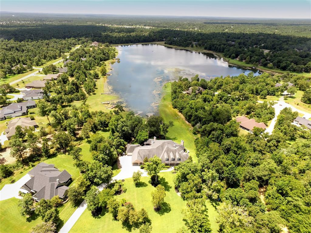 Come experience this tranquil custom Southern-style executive's retreat nestled on 2.8 acres overlooking a picturesque lake within minutes of The Woodlands. Everything you need to unwind after a long day has been meticulously planned: beautiful mature landscaping, gracious front porch, expansive outdoor living area facing the water with summer kitchen & fireplace, personal boat dock.  The home is designed for entertaining with large living spaces, including formals, private study, gourmet kitchen with GE Monogram/Thermador Appliances & wet bar.  The master suite features a fireplace & private patio area with a water fountain.  A spacious walk-in closet, spa tub, elegant his & her vanities, private exercise room complete the luxurious master bath.  Two secondary bedrooms & Hollywood bath are also located on the 1st floor.  The 2nd floor boasts 2 additional bedrooms, game room, wet bar, & home theatre.  Whole house generator, 4 oversized garages, air conditioned workshops, much more.
