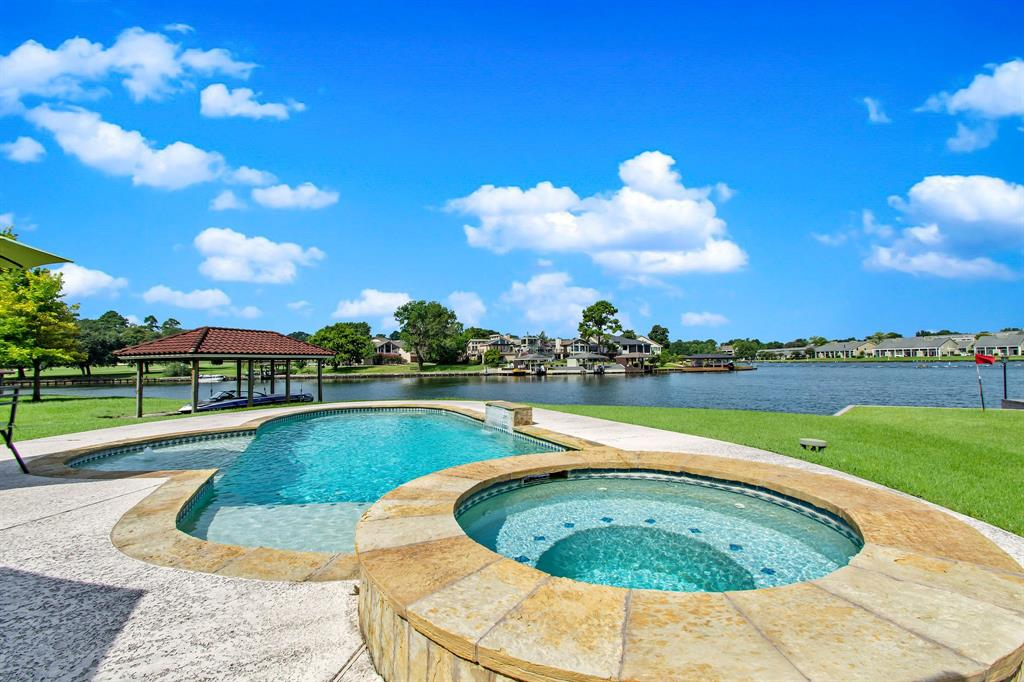 Waterfront home nestled on an oversized, bulkheaded, open lot in the gated community of April Sound complete with powered, covered boat lift. Den includes surround sound system and a built-in entertainment center.  Backyard oasis includes retractable, remote-controlled, powered canopy  and surround sound speakers. This home has 4 beds down including the Master bedroom with an incredible view of Lake Conroe - all with full baths. A Guest suite and Game room on second floor with full baths in each one. An additional guest bedroom downstairs includes bath also. 7 full baths in total plus a half bath for the pool area. The 2-car garage includes an additional space for golf cart. Additional features include tile roof, electric blinds, engineered hardwood floors and tile throughout with no carpets. All furniture and furnishings are included in the list price. Ready to move in!!