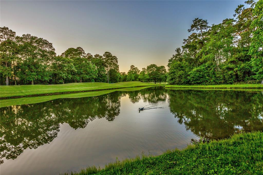 WATER VIEW - NEWLY RENOVATED 1-story backs to the 3rd hole of the Palmer General course. Custom Tom Cox beauty is ready for move-in! Light, bright & modern updates include formal living/dining; open concept kitchen & den, ventilated greenhouse/sun room; master & guest suite down w/optional study. Highlights freshly painted interior & exterior, gorgeous mill-work, updated hardware, lighting & plumbing, modern finishes, Nest Thermostats & automated smart sprinkler system. All new flooring: solid wood, new Travertine & carpet. Kitchen features brand new SS appliances, dry bar & beverage cooler, new counter tops. Beautiful paneled walls, accent beams & updated baths, master bath w/cedar closet! Upstairs 2 suites/optional game room; climate controlled storage w/build out option. Beautiful balcony views of the pond and golf course! A spacious backyard is home to a large patio w/extended cover, water feature and lush gardens, a true retreat in the heart of The Woodlands. Never flooded!