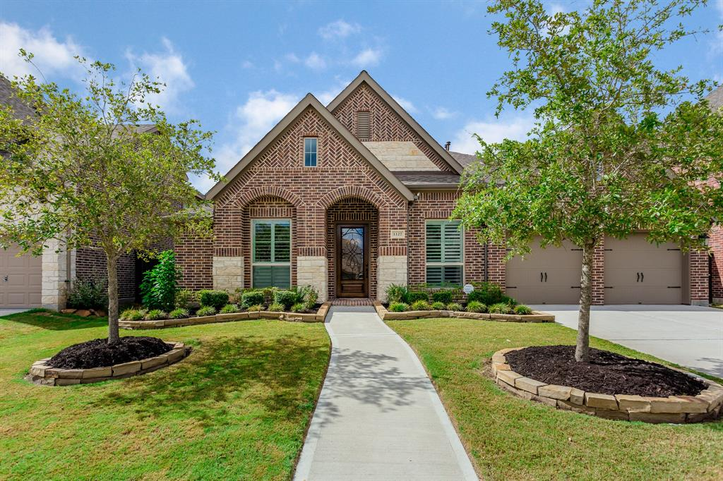"First Houston-area development centered around a community farm, the first ""Agri-hood"" with a Farm Club to learn how to grow your own food. The Harvest Green Community offers some of the Best Family Living with TONS of Events, 800 Acres of Farmland and Farmer's Market. This beautiful home features split bedrooms and open floor-plan.  Huge island kitchen overlooks the family room that includes a gas log fireplace.  So many extras like plantation shutters throughout the house, drapes, water softener, full brick exterior, covered patio, full sprinkler system, mud room, extra drainage.  Wood floors in the dining and study.  Carpet only in the bedrooms."