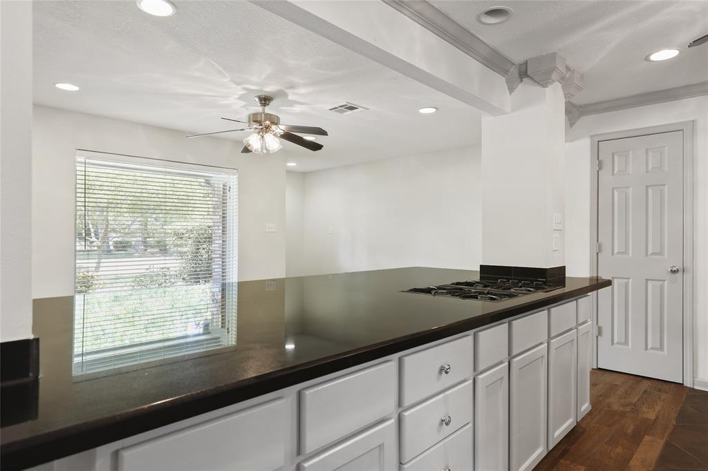 Large center island with granite counter-top and gas range.