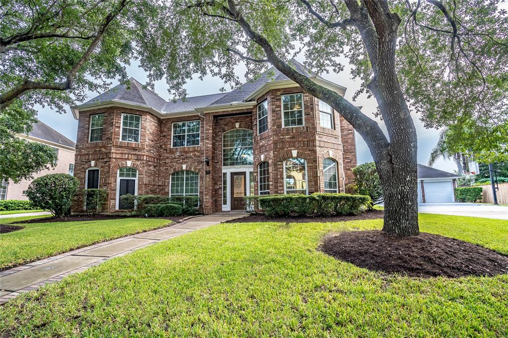 Come and make yourself at home in this gorgeous Frederick Harris home! This gem is situated on an 11,000 + sq. ft. lot, on a beautiful tree lined street, in a private and gated community. You will have a great view of the lake just steps away from your front door! Well manicured lawn, mature landscaping, in ground swimming pool and hot tub. Property boasts 5 bedrooms, 3.5 baths, 3 car detached garage and an outdoor kitchen! Open kitchen, family room concept! The grand kitchen offers granite countertops, large island and an abundance of cabinetry space. First floor master suite is truly a retreat with wood flooring, a fireplace and an updated bath.Walk-in closets, tub plus shower and more! On the second level you will find nice size secondary bedrooms, a spacious game room and media room! This home is great for entertaining family and friends! Zoned to FBISD. Walking distance to The Club, community parks, trails, tennis courts and pools. Make this home yours!