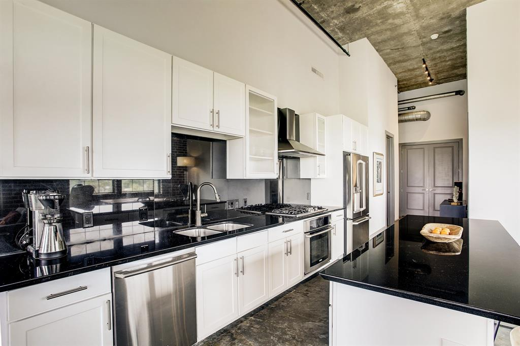 Another perspective of the kitchen which includes a vented hood over the stove. The entry to the condo is around the corner to the left, at the back of the photo.