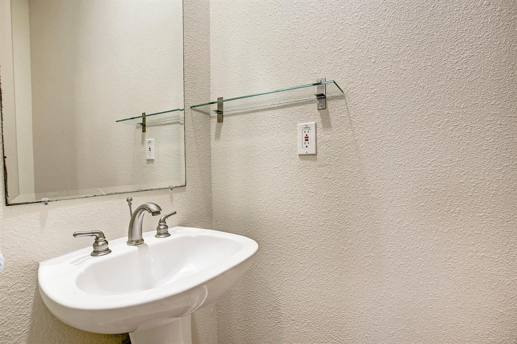 The first floor half bath is discreetly tucked at the end of a short hallway off the kitchen.