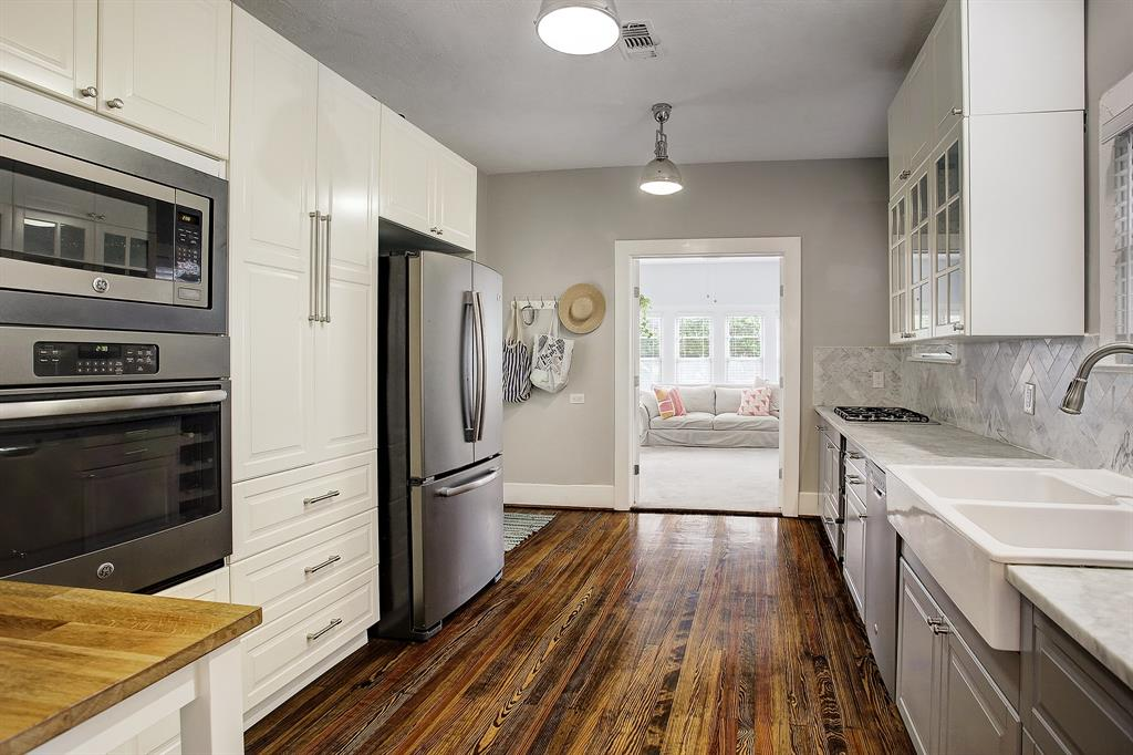 The completely updated kitchen includes a farm sink, carrara marble countertops, wine storage and stainless appliances.