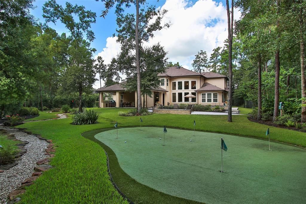 Stunning custom 5 bedroom home nestled on a wooded 1 acre cul de sac lot in Benders Landing Estates.  Professionally landscaped front and backyard that rivals lush resort life w/ glistening pool/spa, putting green, fire pit, dry/river creek, oversized covered lanai w/outdoor kitchen and plenty of decking for rest and relaxation.  Entertaining will be a dream! Interior of the home is filled with elegant architectural touches. Lovely elevated study and wine cellar to name a few. Dramatic 2 story living area overlooking park like backyard w/gorgeous limestone floor to ceiling fireplace. Gourmet chef's kitchen w/huge island w/copper sinks, 6 burner gas range, double oven and built in fridge. Master bedroom overlooks lovely backyard paradise. Popular downstairs guest bedroom &bath that opens to covered lanai area.  All bedrooms are generously sized with private baths and walk in closets.  Gameroom & media room equipped with surround sound. Wonderful location close to clubhouse and lake.