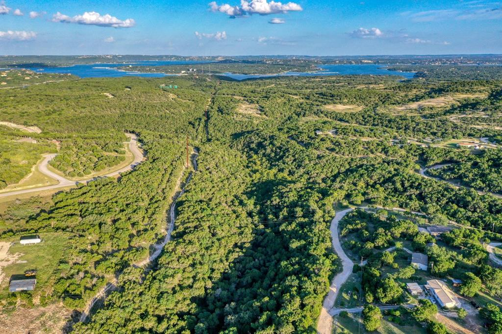17+ hill country acres right in Lago Vista! Approx 3 flat acres for building, Adjacent to the premier North Lake Travis community- The Hollows. Some possible uses: a large and private estate, a compound of typical homes, a zip line park, mountain biking park, tiny home community, hiking trails and more! Beautiful trails and terrain are part of this acreage. A waterfall and wet weather creek run through the middle of this oasis. There is a small building/structure on the property, but it is not livable.
