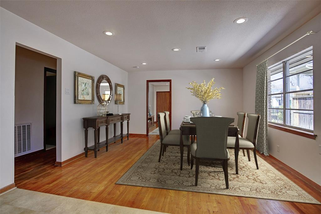 Looking toward the living room and front door, with the kitchen behind, is a space that serves equally well as a dining room or second living area, or even both. This room has been virtually staged.