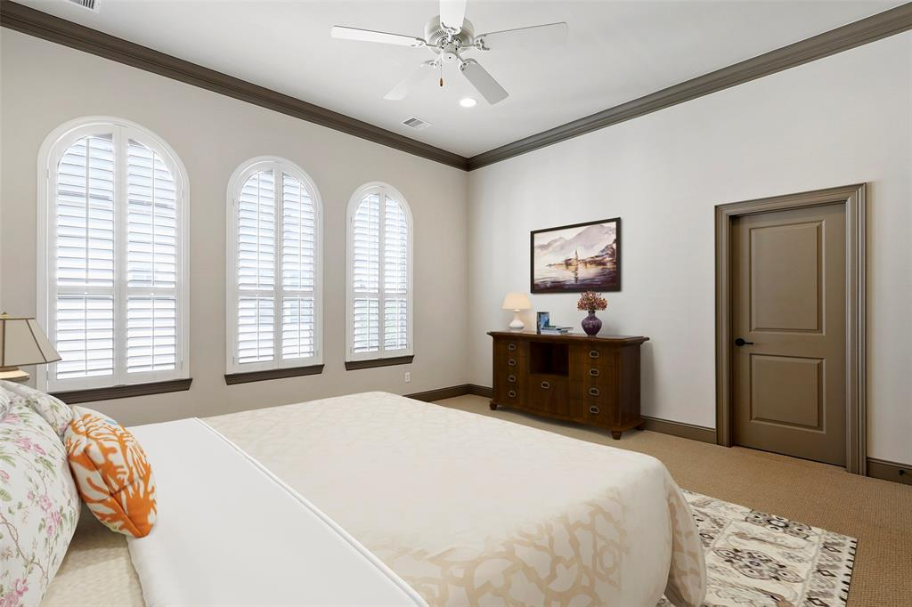 Spacious master bedroom with lots of natural light and plantation shutters. This photo has been virtually staged.