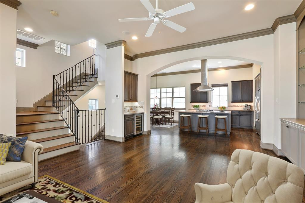 The open floor plan features wood floors, beautiful built-ins and crown molding. This photo has been virtually staged.