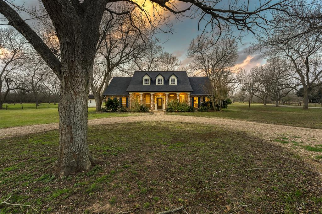 Welcome to this fine country property upgraded with a modern touch. The sellers have spent a year to carefully remodel this country gem. Snuggled among the pecan grove, this 1 story custom home offers privacy & serenity. The 3000 sqft home sits on 6+ fenced acres with 3/4 bedrooms, 2 full baths & 2 half bathrooms, a 3-car garage with attached porte-cochere. The land features an insect control system, circle driveway, an enclosed outbuilding with electric & water & a covered parking slab fit for an R/V that also has electricity running to it. The stainless steel kitchen appliances are surrounded by custom-built cabinets with upper/lower lighting. The oversized utility room has lots of counter/cabinet space & a sink with plenty of room left for a refrigerator. The picture windows along the back invites you to sit & enjoy the view. PROPERTY HAS NEVER FLOODED! Low taxes, no dead restrictions, & plenty of land to customize the outside; come take a look! Make sure to view the virtual tour!