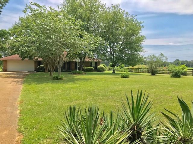 Country charm setting for this custom brick home on five beautiful acres. Large Living Den with brick surround WBFP and mantle will be focus of this wonderful family sized room. Spacious 4 BR, 2 bath floor plan so comfortable for everyday living. Easy to enjoy Kitchen with granite countertops and a large breakfast bar. From the breakfast room walk out onto a covered deck -  ideal for family and guests to enjoy a meal or just time with one another. Attached 2 car garage plus a separate detached garage or shop on a slab with overhead door and walk in door entrance. Plus there is a separate storage building.  Public water plus a water well.  Large shade trees, fenced pasture for your horse to graze, lots of road frontage and so much more.  Decorative fencing at front of house and entire property is fenced.  Come see and make this one your family home for a generation to love and treasure.