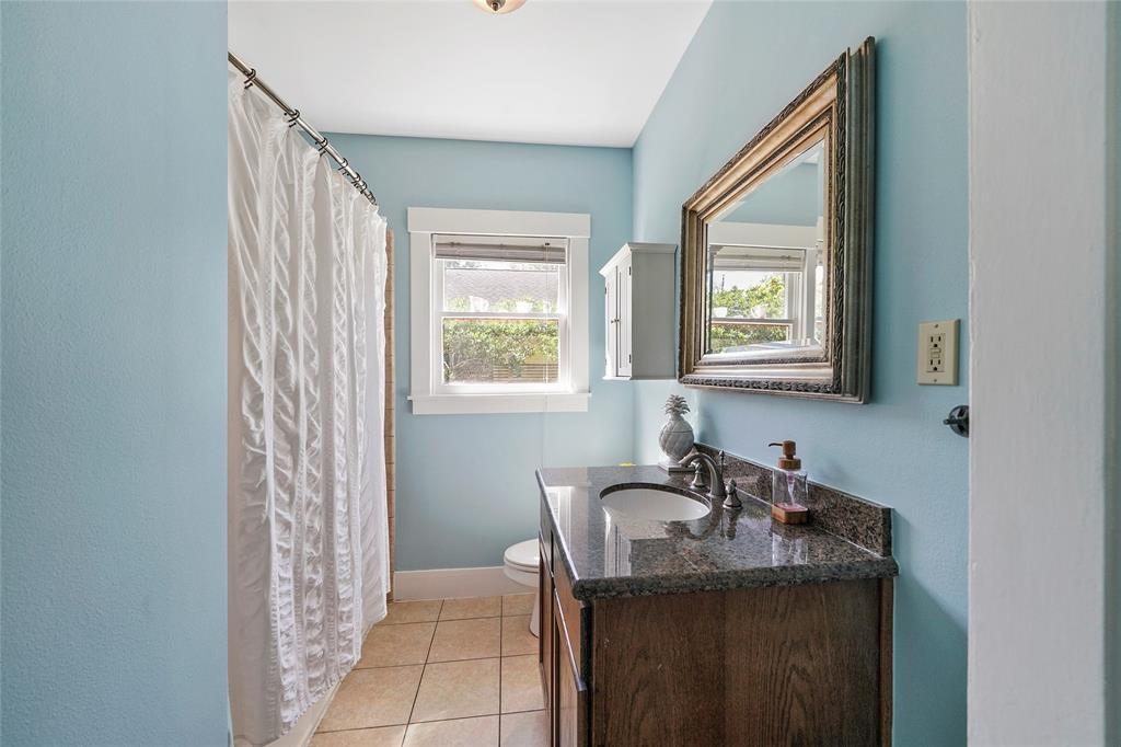 Attractive bathroom with granite vanity, tile, and tub/shower combination.