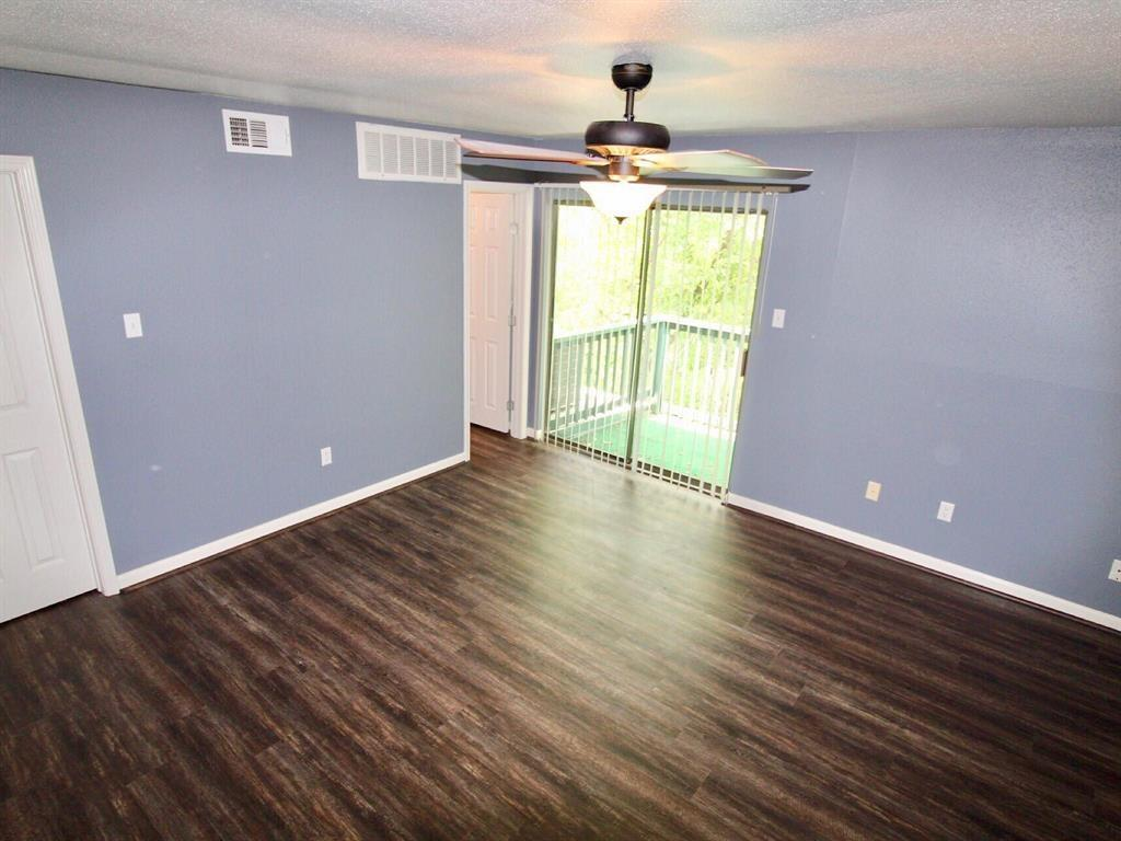 Large master bedroom with view of upstairs balcony.