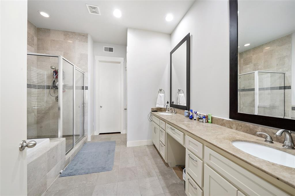 Large master bathroom includes double sinks, framed mirrors, and a large stone counter-top.