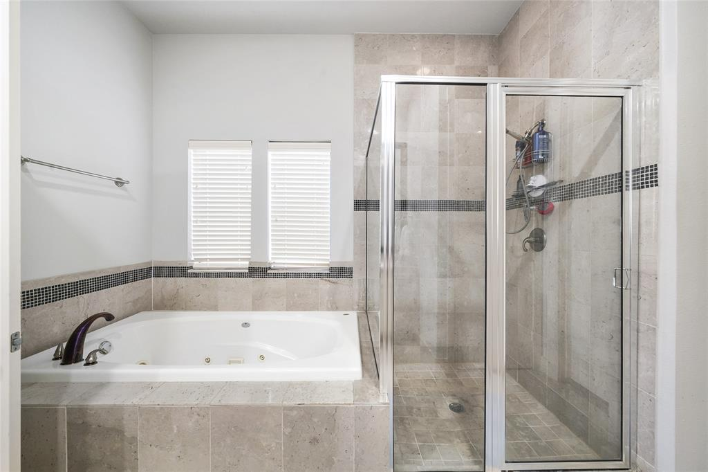 Whirlpool style tub with separate shower. Shower and Tub include stone tile surround.