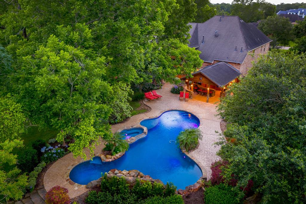 """Positioned in the elite acreage estate section of Bees Creek on 1.28 acres!  This stunning home designed by David Powers is encompassed with mature trees & lush landscaping.   The professionally equipped open gathering kitchen & family room are perfect for hosting large gatherings. Step outdoors to your secluded back terrace retreat offering a """"grand"""" sized heated saltwater pool & elevated circular spa.  The expansive open air covered living & kitchen areas are highlighted by wood plank vaulted ceilings.  An exterior half bath offers a changing area, sink, and water closet.  The executive office luxuriously appointed to accommodate a days work features rich wood paneling, custom built ins, and box beam ceiling. The master suite and a highly desired secondary bedroom with en-suite bathroom are located on the main floor.  Upstairs amenities include media room with open air terrace & gameroom with wet bar.  Low tax rates, zoned to highly rated FBISD!"""