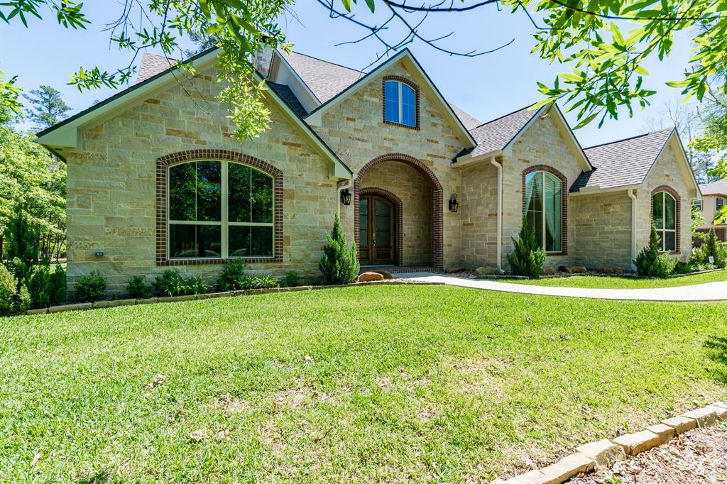 "Better than new, Built in 2016, Gorgeous custom home, nestled behind a lightly wooded area, stone, brick and stucco façade, double glass doors welcome you into a spacious foyer and living area with a floor to ceiling stone fireplace and built-in bookshelves, High end details throughout, including 2x6 studs in lieu of the standard 2x4's, wood planked ceiling on covered patio, stainless appliances, 12' ceilings, hand scrapped wood floors, 20"" tile, exposed wood ceiling beams in living, dining and master bedroom, huge master with large sitting area, all bedrooms down with private baths, unbelievable game room and media room upstairs, tons of storage throughout, decked walk-in attic space, outdoor kitchen with 30x16 covered patio, true 4 car garage, wooded private lot. Home has an additional 220 sq. ft. of living space in the game room which is not reflected in tax records.  Easy access to all major highways, dining, shopping and highly rated Conroe ISD. Country living at it's best!"