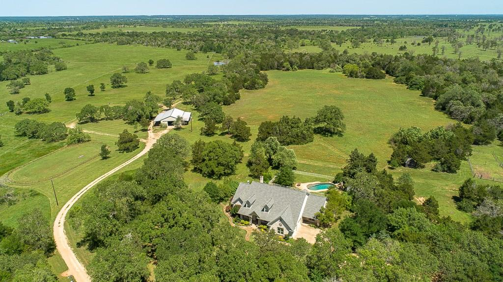 Welcome Home to Turkey Track Ranch! ~ This incredible, custom 4,266 sf home has many architectural details, high ceilings & features 3 bedrooms on the main level, 3 1/2 baths, an office, music room, large bonus room/4th bedroom, screened porch & pool. Surrounded by 102+/- breathtaking, gently rolling acres with many large oaks, a pond & equestrian facilities, all within 45 minutes of Austin. You don't need horses or cows to appreciate this paradise for all ages & enjoy the peaceful country lifestyle.