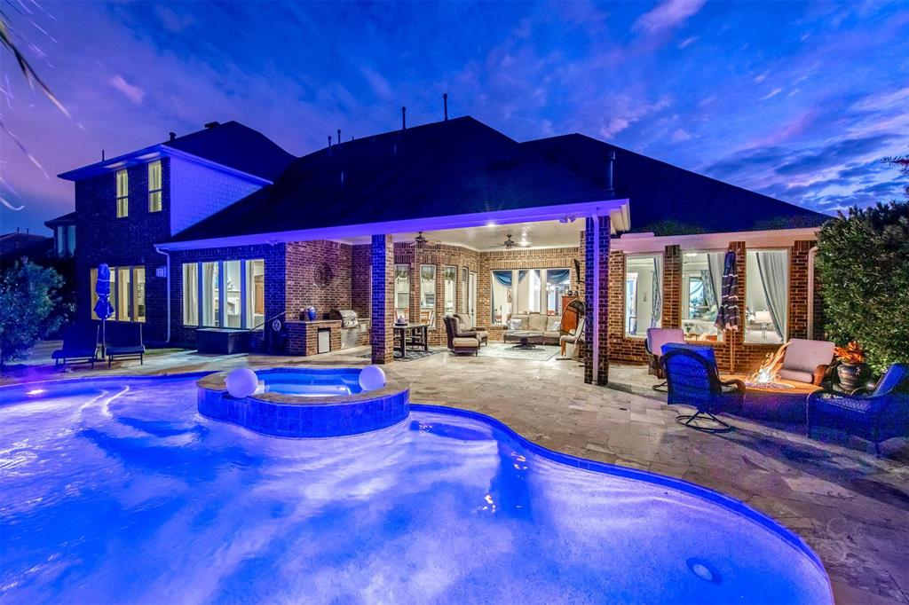 GORGEOUS LAKEFRONT LUXURY HOME with a sparkling POOL/SPA and OUTDOOR KITCHEN! Step out back of this stunning home to take in the beautiful lake view or enjoy through all the windows along the back of the house!  Fabulous 5,242 sf masterpiece presenting 5 large bedrooms-27 ft luxurious master suite w/an amazing water view & sitting room w/fireplace. Bath spa w/whirlpool tub and walk through shower.  2nd bedroom down w/bath in-suite.  Rich hardwood flooring throughout, Spacious gourmet kitchen w/double ovens, exotic granite & everything trending! This home offers a great open concept that's great for entertaining. Featuring a formal dining, study w/ French doors, and an expansive living room w/ a view of the your outdoor paradise. Game room & media are down, so upstairs offers privacy to the 3 large secondary bedrooms w/baths. Two generous sized hidden closets!  Zoned to acclaimed Katy ISD. Come experience the elegant luxury that this exclusive home provides!