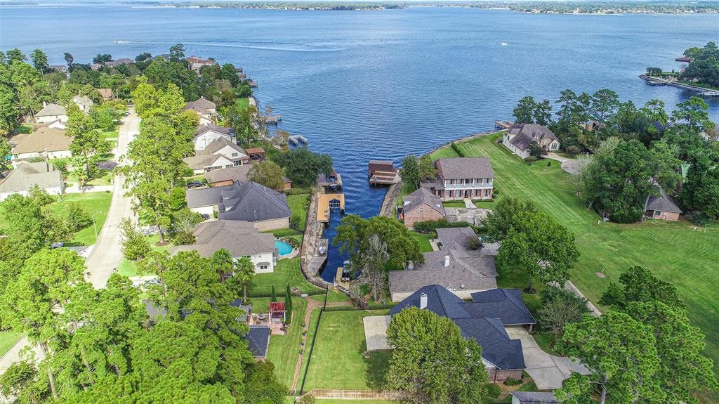 FEEL LIKE YOU ARE ON VACATION EVERY DAY! This home is ON LAKE CONROE with a NEW BOAT LIFT right off of WIDE OPEN WATER! You also have a beautiful custom home that is elegant & will impress you! WIDE OPEN spaces inside with lots of windows for light and lake views. There is a NEW AC, NEW ROOF, NEW BOAT DOCK, NEW PAINT, NEW SOLAR POWERED LIFT, and more! In addition this home boasts a REMODELED kitchen and master bath. All the trimmings with granite and wood flooring and nice large living space for entertaining. The bedrooms are large as well and you also have a possible 4th bedroom or you could use it as a study. This is not your typical lake lot because it has SPACE! You have a large fenced backyard, and a large back patio space to grill out or enjoy the lake and sun. This home is also on a private road that offers low traffic and there is no neighbor across the street because you have a greenbelt that is a great space to play! This is all at a price you can't beat so come get it quick!