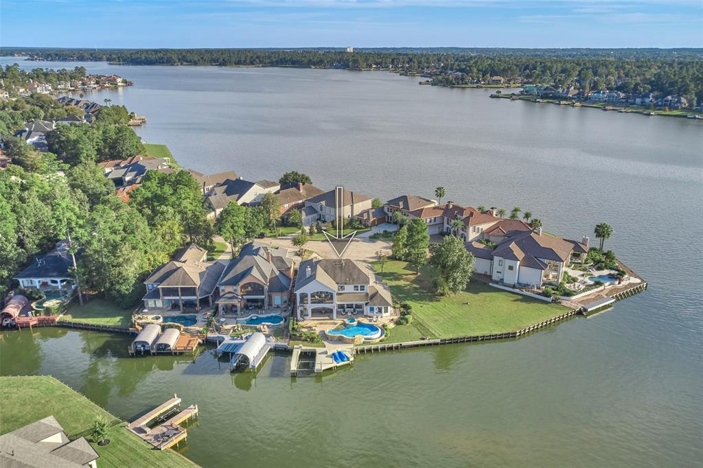 Rare find...Everything you could want in a LAKE HOME. Custom built with high end finishes, infinity pool/spa, outdoor living area w/ fireplace,summer kitchen, pool bath and VIEWS for miles!!! Boat/Jet Ski lifts.Top of the line construction with 60 builder piers under slab, central vac, double crown, 3 car garage, surround sound,GameRM with wet bar, huge media RM, Wood flrs, chandelier light fixtures, chef kitchen with upgraded appliances...Perfect for entertaining. See feature Sheet!!