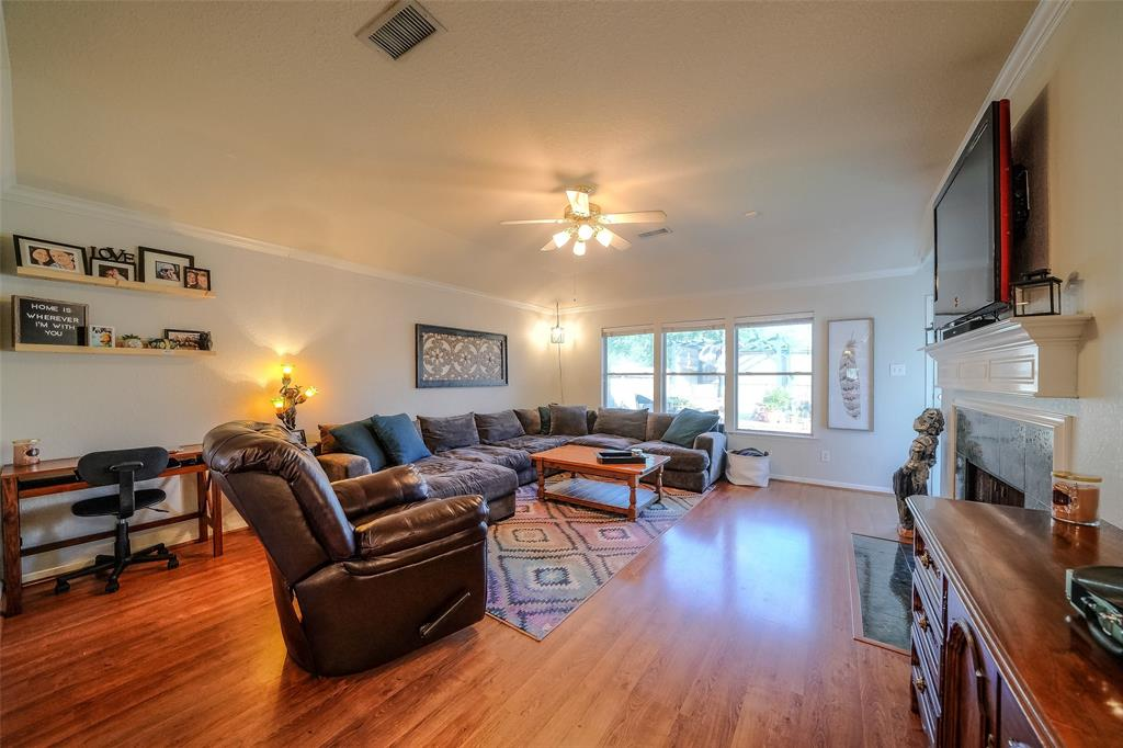Spacious Living Room currently features an office nook, large windows with lots of natural light and Gas Log Fireplace at the heart of the room.