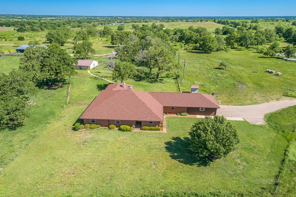 Country Estate on 14.7 acres only 4 miles from Giddings. Approx. 1,300' of paved driveway will bring you to the 3,504 SqFt Home which had an interior makeover & Master Suite addition completed in 2013. 3 Bedrooms, 3 Bathrooms, Living Room w/ Fireplace, Large utility room, Huge Bonus Room(was used as workout room & media room), & 2-car garage. Concrete walkway to the additional 30x30 metal building on concrete slab w/separate electric meter.Previously used as an office.36x52 Barn and cattle working pens. Chain-link fence around house.Perimeter fenced & cross-fenced for cattle. Scattered Post Oak trees. New Composition Shingles in 2018. House supplied by Lee Co. Water & 450' deep water well. Aerobic septic system.2 HVAC units.All updated double-pane windows. Master Suite addition w/custom bookcase & ceiling. Gas fireplace, window seat w/extra storage; Custom Cabinets in Bathroom with tiled walk-in, Rainforest multi-jet shower & Programmable Sauna Combo and spa Jacuzzi Tub. Ag. Exempt.