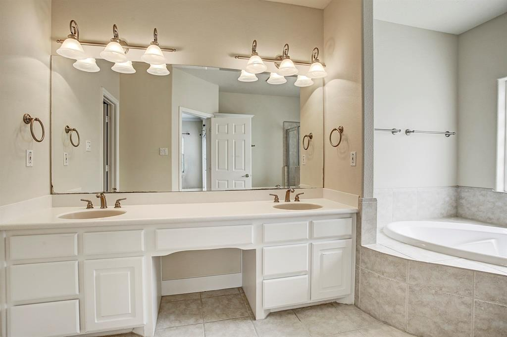 The master bath is beautifully appointed with dual sinks, a vanity area, separate jetted tub and shower, and a private water closet.