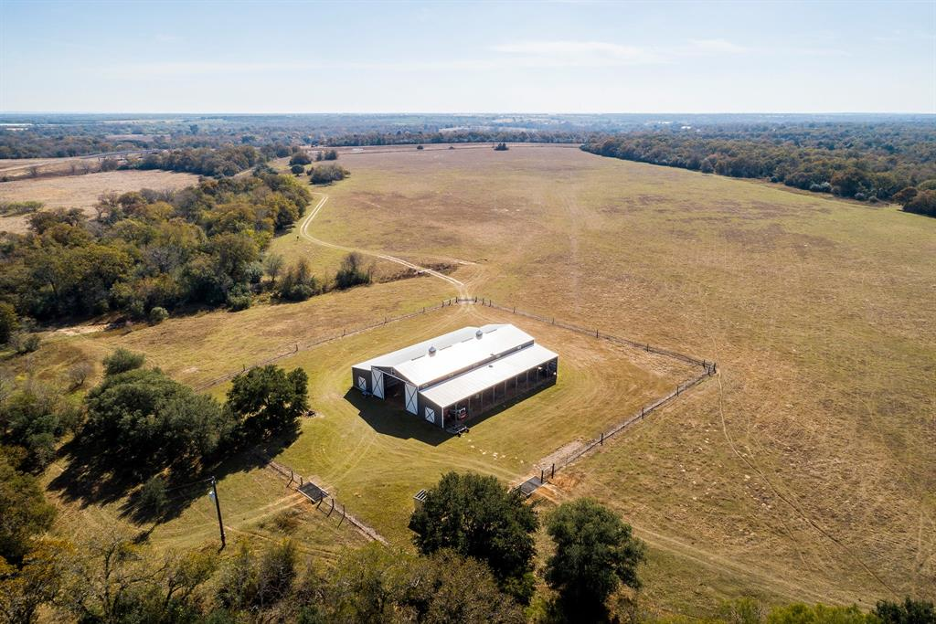 NEW PRICE! 137+ acre ranch in rolling hills of Gonzales County, TX,  move-in ready! 2 ponds, seasonal creek, pecan, post oak, mesquite trees.  Approx 130 ac surrounded by high game fence, includes 200 inch class Whitetail genetics. Ranch features 8,000 SF barn built in 2012 w/2,000 SF 2/2 barndominium (built off of the main barn's lean to). Wide open kitchen & living area. Kitchen w/large island, breakfast bar. Baths walk-in showers. Barn area of 4,000 SF center aisle of barn is wide open for farm equipment, feed, hay, storage. 18' sliding barn doors on north & south ends, making it accessible for heavy/large equip. 1 - 50-amp & 3 - 30-amp RV electrical outlets. Attached to the barn's west side is 2,000 SF lean to that can also be used for storage & is accessible from outside of barn. 4.5 acres w/low fence working area joined by holding pens for cattle. Ranch water supply comes from 300 ft well drilled in 9/2012