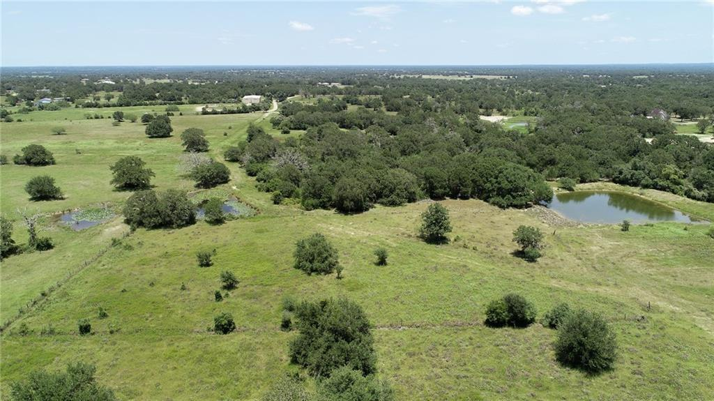 Ag-exempt acreage centrally located between Houston and Austin just north of HWY 290. 25.471 partially wooded acres with spring fed pond that the owner stated did not go dry during the drought. Perfect place to build a weekend getaway or a new home! This listing is for tracts 3 & 5.  Property has a well (the pump has been removed and will need to be replaced if you want to use the well). One additional tract is also available with large metal building (10.563 acres) or all three tracts together as 36.044 acres. Restricted against mobile home parks.