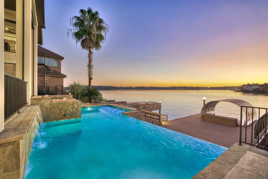 Beautiful waterfront with vast views of Lake Conroe and a fabulous infinity pool w/waterfall & spa and many updates!!! Many custom features: 3 car garage w/polyaspartic floors/workbench/cabinets, circle driveway, outdoor kitchen w/ refrigerator & sink, 31'x13' covered back porch w/ $25k in retractable screens, Trex decking, covered boat slip w/lift, jet ski lift, Lutron lighting & LED lights, outdoor TV & speakers controlled from ipad, pecan wood floors, plantation shutters, water softener. Inviting double entry doors & soaring 2 story foyer. Open kitchen w/ high-end appliances & pot filler, 2 subZero refrigerators, gas stovetop, butler pantry w/ wine cooler & sonic ice maker. Study is on the mezzanine level w/ sweeping views of Lake Conroe. Inviting master suite w/ impressive 16'x11' closet. Gameroom upstairs w/ 3 sizeable secondary bedrooms and attractive screened-in balcony. NEW ROOF, new exterior paint, & many other updates. Social membership included, sports membership available.