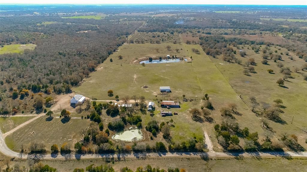 25.7 acres in Lee County with easy access from Hwy 290. If you want your own working ranch, this is the whole package! Completely fenced and some cross-fencing. Includes a barn, hunter house, small cabin overlooking one of the 2 ponds, livestock trailers, tractors and all implements and farm equipment. Cattle and cattle equipment are also included! Get around the property on the Trx450fm four-wheeler. Two 48 foot storage trailers are full of parts and tools and an additional trailer used as a shop already hooked up with electric. 2015 RV hooked up and ready to move in and a Mark III van. New aerobic septic system. Two electric service meters, 3 gated points of entry. Mature trees scattered over the property. No restrictions. AG exempt. Minerals negotiable.