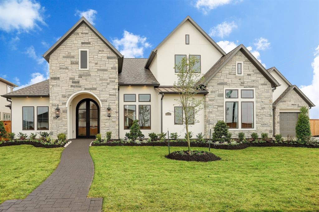 """RECENTLY COMPLETED AND READY FOR MOVE-IN!  Located in the gated """"Water's Edge"""" neighborhood within Towne Lake, this brand new offering by Jamestown Estate Homes is one-of-a-kind, with a stone and stucco exterior and modern touches.  The first floor has a master bedroom and guest suite, study, game room that opens to a covered patio, and an airy kitchen/breakfast/family room with high ceilings.  Wood floors throughout most of the first floor.  Upstairs features two large bedrooms with private baths, and a media room that can be converted by builder to a fifth bedroom.  The nicely-landscaped backyard is HUGE and open on one side to a large greenbelt. Patio is plumbed for an outdoor sink and BBQ. Custom amenities include:  Thermador appliances, high-efficiency A/C's, custom trim and appointments and upgrades throughout!"""