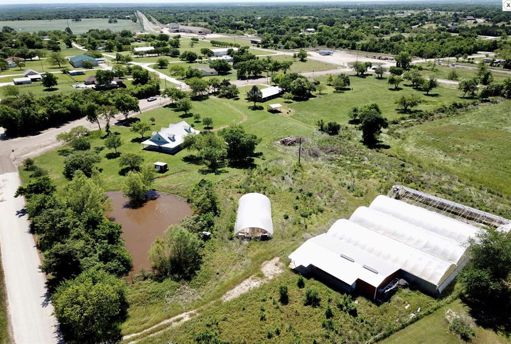 Lot 1 & 3 of Millican Stop is being offered together with the five greenhouses, the shop/office building, and the pond.  Approx. 250 Ft of FM 159 frontage and approx. 300 ft. fronting Kathy Fleming Rd. This property can be commercial and or residential. The 1800 SQ FT shop features facilities to support the former growing and packing operation. It could be utilized as almost anything. Reopen the greenhouse growing facility or convert into almost anything. The pond was used for irrigation. Public water is available.