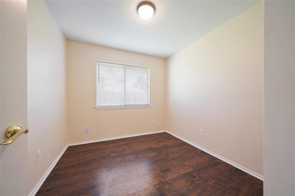 First bedroom with laminated wood floors.