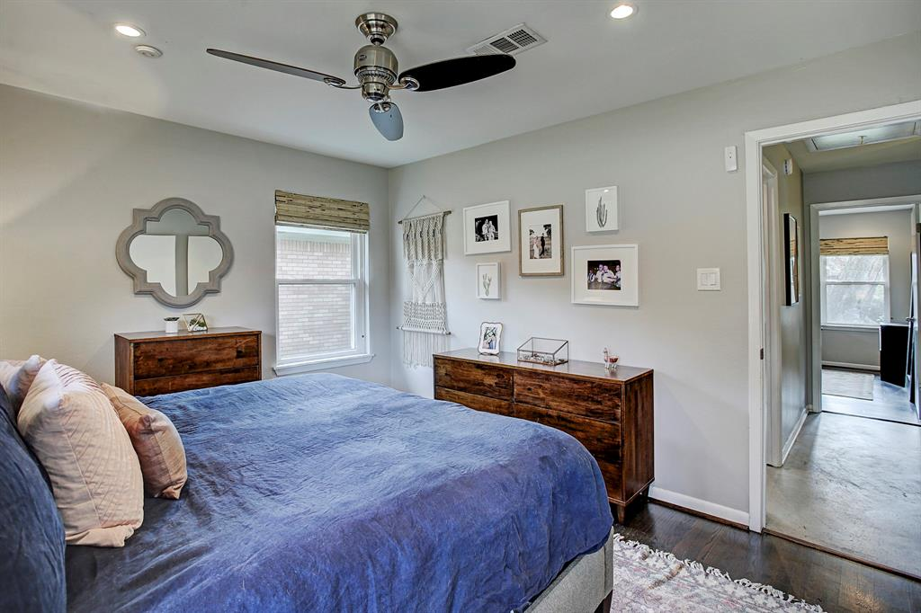 Master bedroom features original hardwoods, neutral paint, Hunter ceiling fan, recessed lighting and en-suite half bathroom.