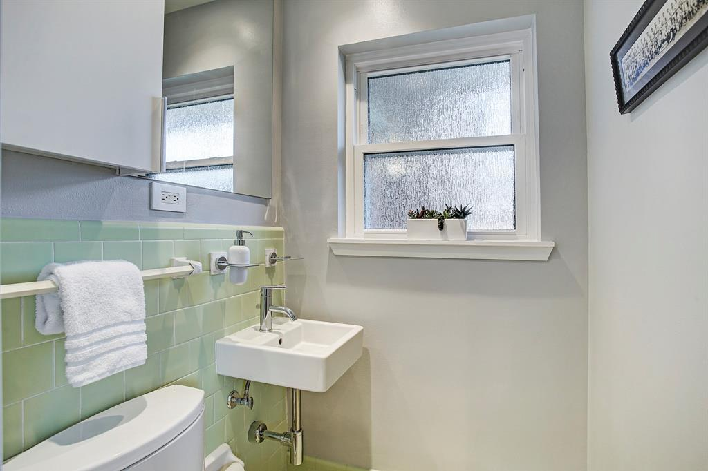 Light-filled half-bathroom features updated fixtures and cabinet for storage, new privacy window and neutral paint.