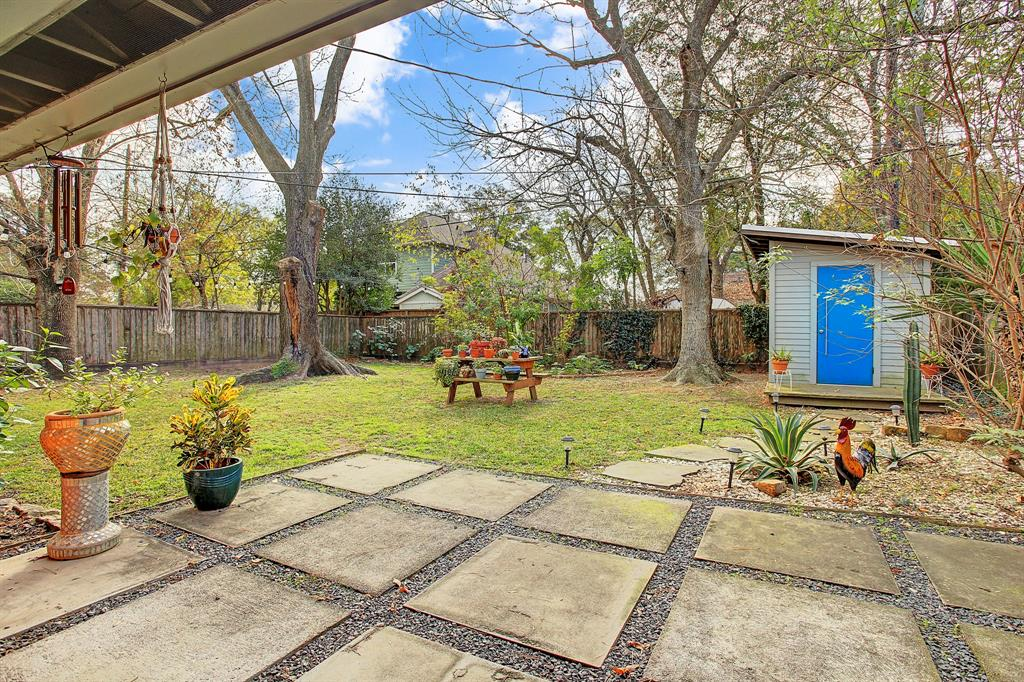 Lush backyard oasis features concrete paver patio, stylish storage shed and multiple trees for shade. Owner has landscaped flower beds with hibiscus plants and other flowers.