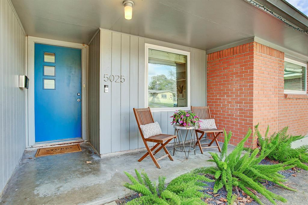 The inviting concrete front porch features a covered space for outdoor furniture, a Ring doorbell and foxtail ferns.