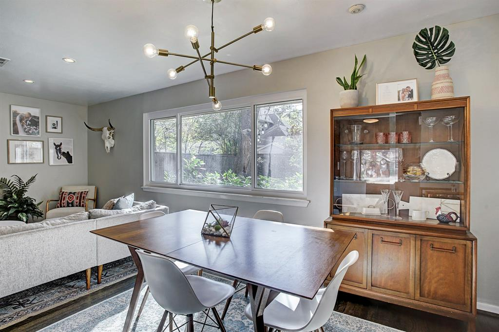 Dining area features a modern light fixture from West Elm, original hardwoods and beautiful view into the backyard.