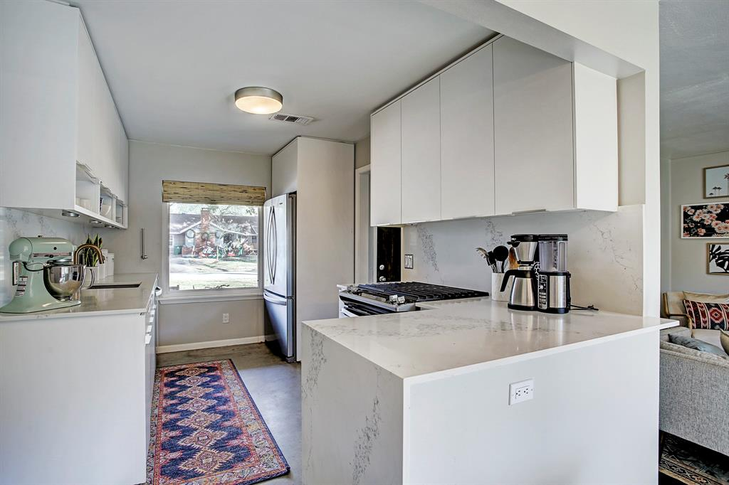 Beautiful remodeled kitchen features quartz counter tops with waterfall ledge and matching back splash, concrete floors and neutral paint. Whirlpool counter depth refrigerator fits the space perfectly. Picture window overlooks the front yard.