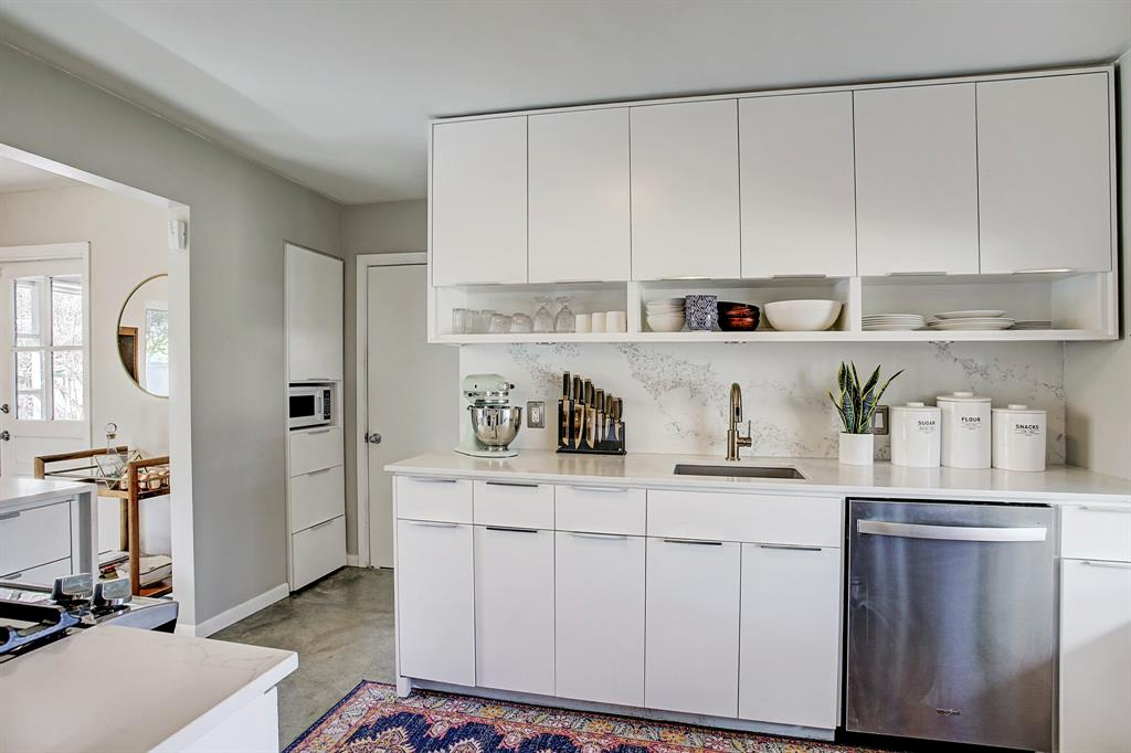 New brass Delta faucet, granite sink and Whirlpool dishwasher installed in 2019. The modern flat-front cabinets with open shelving have been refinished. Plenty of counter space for food preparation and entertaining. Door leads to converted garage.