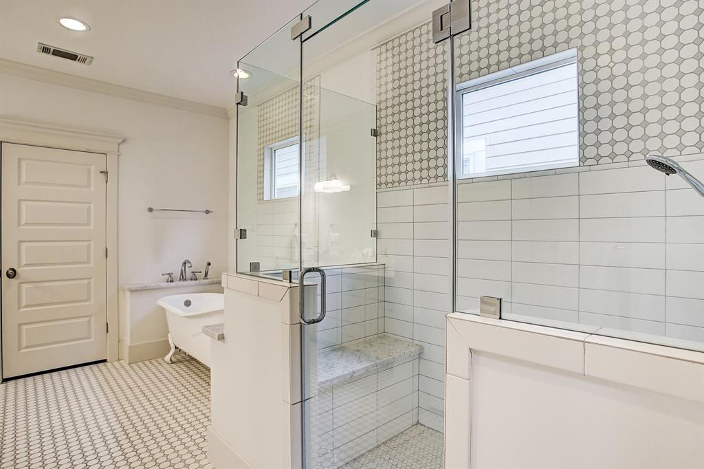 The oversized, frameless glass shower stall includes bench seating.