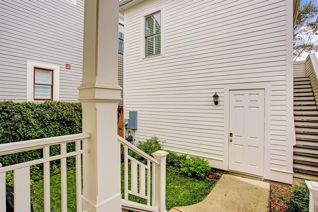 A covered back porch leads to the yard, garage, and garage apartment.  Not pictured, the alley is wide allowing for ample turning radius into/out of the garage.