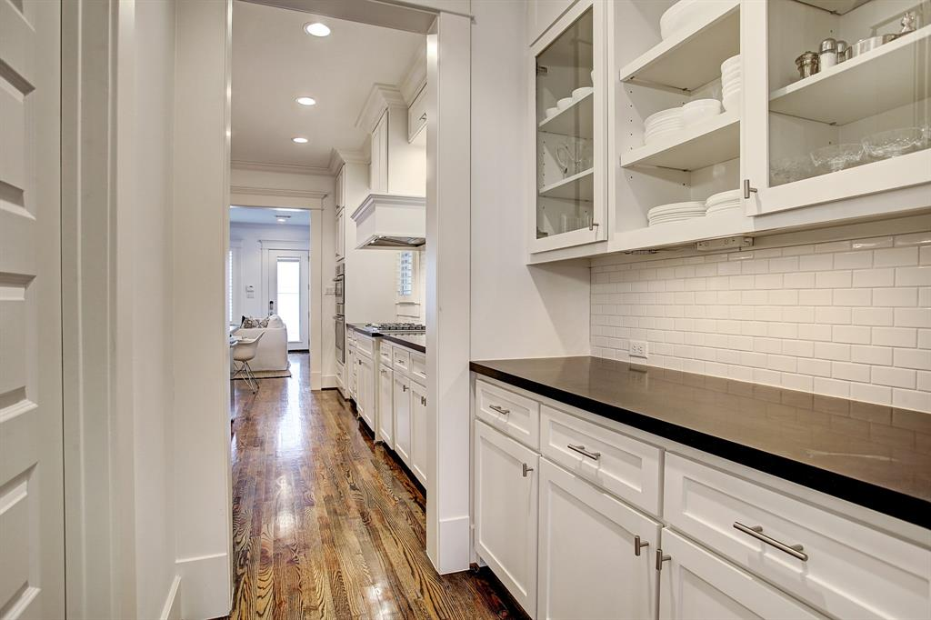 Between the dining room and kitchen is a walk through butler's pantry with wonderful glass front cabinetry, as well as a walk-in pantry (door to the left).
