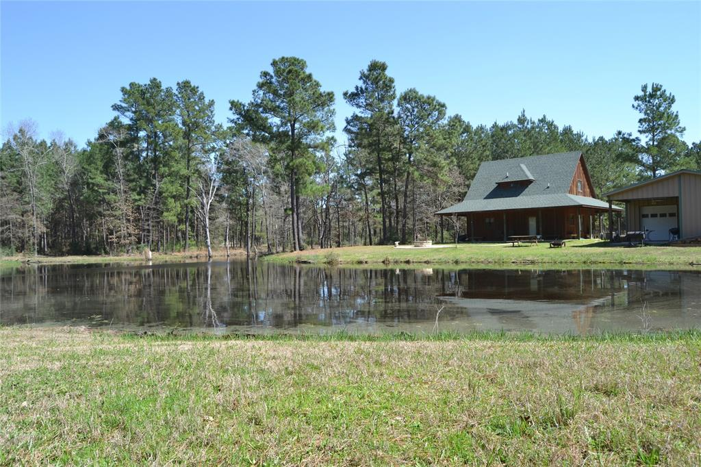 BEAUTIFUL COUNTRY SETTING!   This three bedroom, two bath home has lots of extras! The home sits on 10+ mostly wooded acres overlooking a nice lake. Downstairs, you will find an open concept living, dining, and kitchen area. The master bedroom, bath, and laundry room are also downstairs. Upstairs, there are two nice size bedrooms and a bath. This home is equipped with a security system. The wrap around porches offer great views of the lake, woods, and wildlife. The two-car garage has a covered area for additional parking. Behind the garage, there is a bonus guest room with bath. This property is fenced and has frontage on both, CR 3375 AND CR 3385. Come see this great home today!