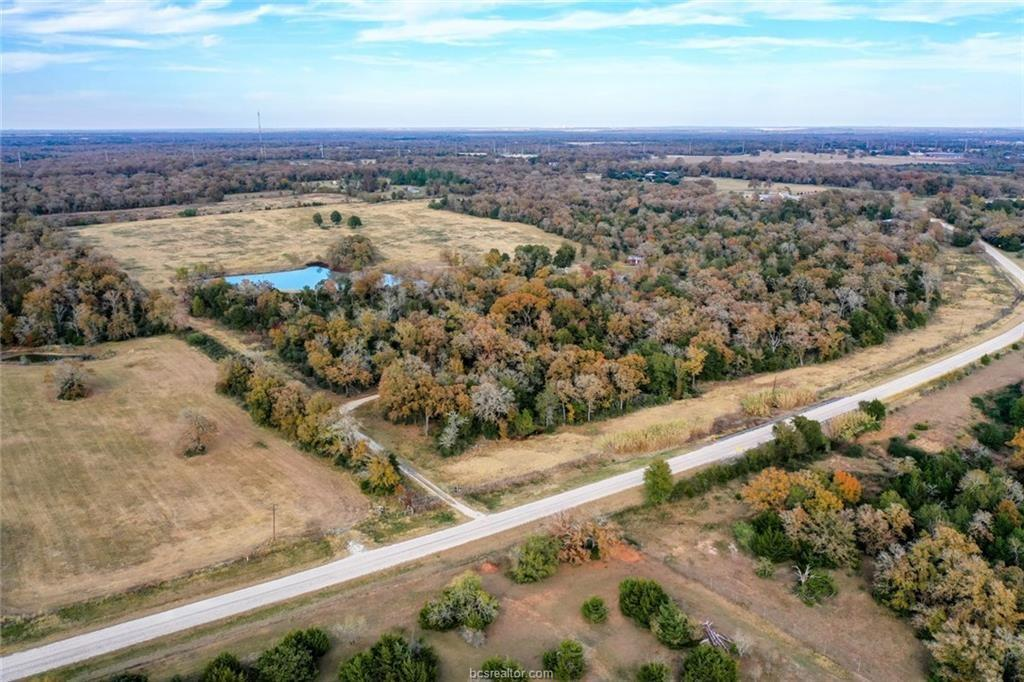 Rare Acreage Find in Millican! Just south of the roar from Kyle Field and a stone's throw away from Highway 6, this gem is accessible from Houston, Austin & beyond. High-fenced on three sides, wildlife abounds on roughly 40% of the property left wooded as nature intended, accented by 20+/- acres improved bermuda for grazing needs. Enjoy weekend stays in the well appointed, charming 1 Bed / 1 Bath rustic cabin with full kitchen and living areas as you make plans to build your dream home on the perfect spot overlooking the 2 Acre stocked pond. Additional improvements include concreted parking area, covered dog runs and 900 square foot equipment barn with overhang. Absolutely Perfect Location!