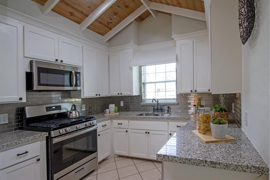 Kitchen features quartz countertops and stainless steel backsplash. All windows have wooden blinds.